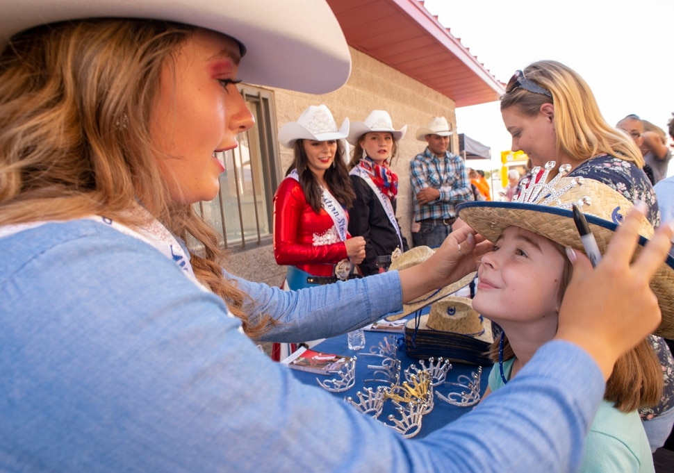 (Rick Egan | The Salt Lake Tribune) Western Stampede Second attendant Madelyn Mundy, puts a crown and a free cowboy hat on Emma Ball, 8 from Syracuse, at the West Jordan Western Stampede Rodeo, Saturday, July 6, 2019.