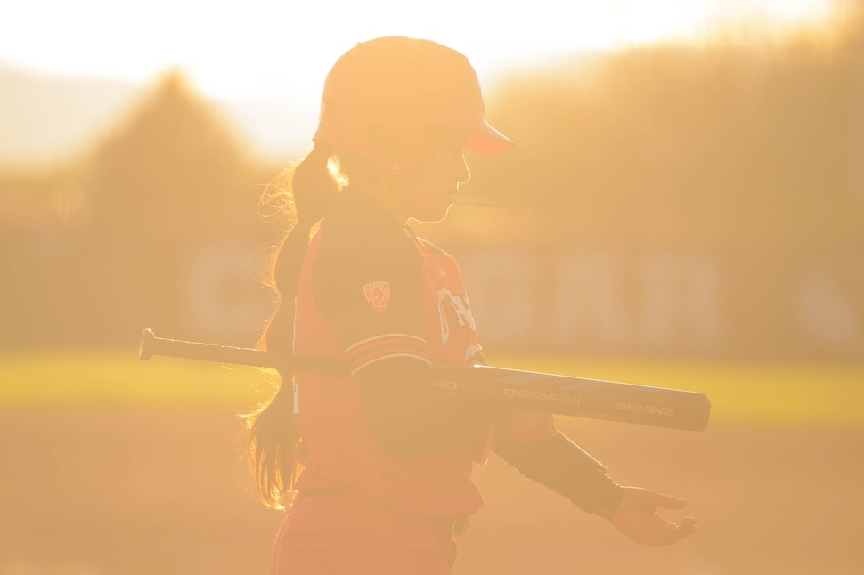 (Trent Nelson | The Salt Lake Tribune) The setting sun flares the lens as Utah's Ally Dickman walks to the dugout. BYU hosts the University of Utah, NCAA softball in Provo on Wednesday May 1, 2019.