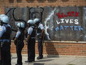 (Pat Nabong | Chicago Sun-Times via AP) In this Aug. 15, 2020, file photo, police officers stand beside a mural for George Floyd in the Chicago neighborhood of Bronzeville during an anti-police brutality protest.
