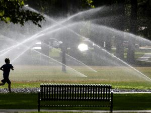 (Steve Griffin  |  Tribune file photo) This July 26, 2017, file photo shows a runner in Liberty Park as the sprinklers flow. Salt Lake City Erin Mendenhall is issuing water conservation orders now because of expected low runoff of and shortages later in the year.   Sprinklers cool down a runner at Liberty Park in Salt Lake City Thursday July 20, 2017.