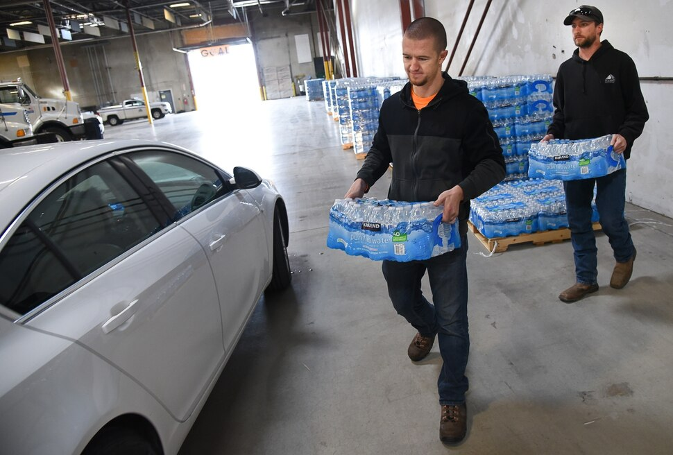 (Francisco Kjolseth | The Salt Lake Tribune) Elliott Purser, center, and Cody Hook with Sandy City load up cases of water into the trunk of a resident at the Sandy Operations Center at 9150 South, 150 East on Sunday, Feb. 17, 2019. The no drink order now applies only to homes and businesses between 1700 East and 2000 East and 10600 South and 11400 South, the city announced Sunday. The city says the problem started about Feb. 6, when a fluoride pump malfunctioned because of a power outage. It flooded the water system with fluoride and that also led to high levels of lead and copper, enough that it made some people sick.