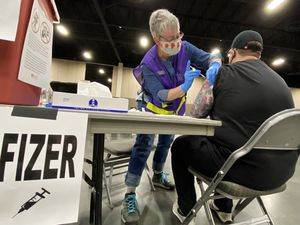 (Rick Egan | The Salt Lake Tribune)  Irene Stukshis administers the Covid -19 vaccine to Stephan Rich, at the Mountain America Expo site in Sandy on Monday, March 8, 2021.