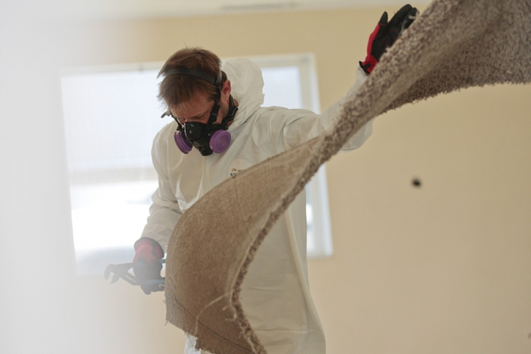 (Evan Cobb | The Daily Herald | The Associated Press) In this Thursday, June 28, 2018, photo, Jared Herbert, foreman for the Meth Mob, removes carpet from a contaminated house in Payson. Meth Mob is a Provo decontamination company focused on cleaning