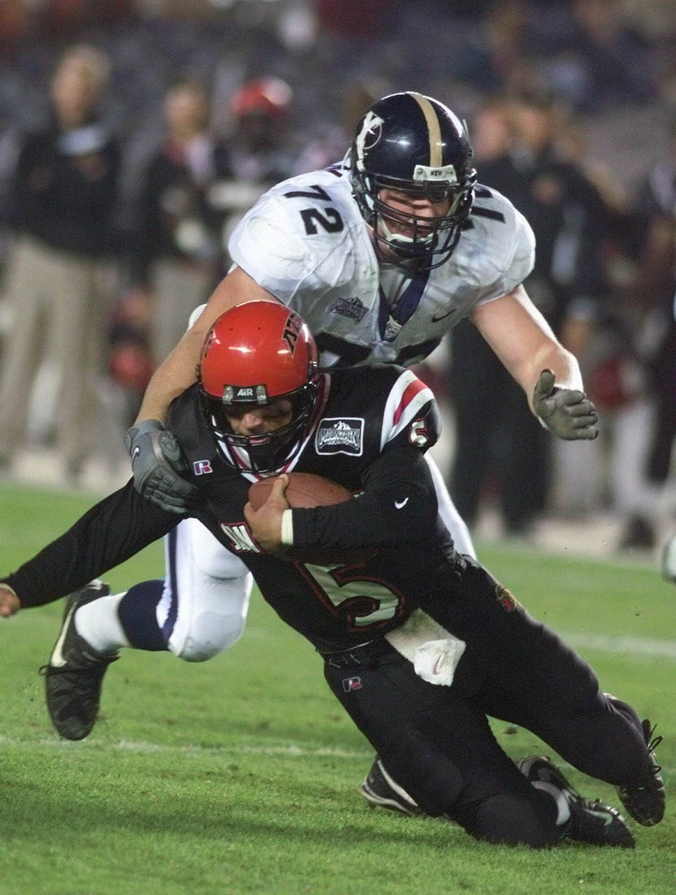 (Lenny Ignelzi | AP file photo) San Diego State quarterback Jack Hawley is buried by BYU's Hans Olsens for a four-yard loss during the second quarter of their game Saturday, Nov. 6, 1999 in San Diego.
