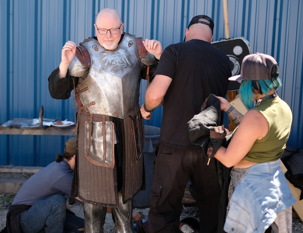 "(Photo courtesy Doug Pasko) It takes a team to get Salt Lake Tribune TV critic Scott D. Pierce into a suit of armor on the set of ""The Outpost."""