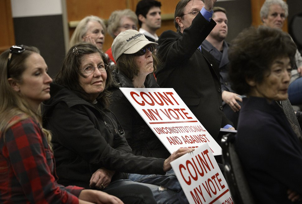 (Scott Sommerdorf | The Salt Lake Tribune) Some who came to the Count My Vote public hearing at the Whitmore Library in Cottonwood Heights brought signs voicing their displeasure with the Count My Vote ballot initiative seeking to select party nominees through a direct primary, in addition to the traditional caucus-convention system, Friday, Oct. 27, 2017.