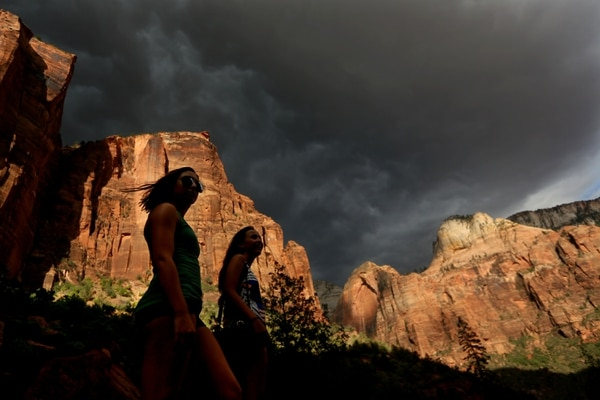 (AP file photo) Hikers look up at a fast moving storm as it makes its way through Zion National Park outside of Springdale, Utah. Many of the country's most prominent national parks, including Grand Canyon, Yellowstone and Zion, continue to set new visitation records — underscoring the issue of a backlog of park maintenance.