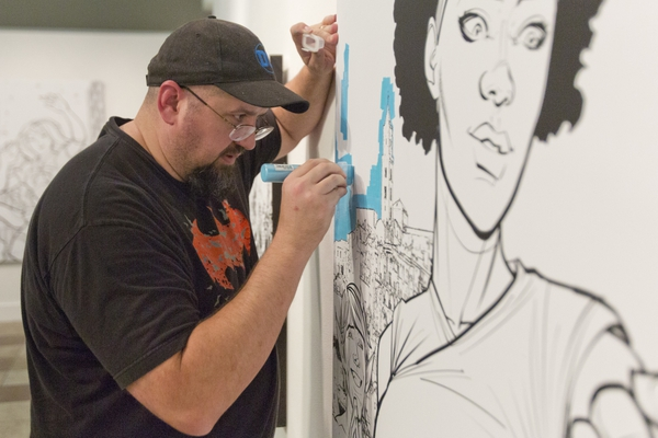 Chad Hardin tests out a paint marker on one of the canvas images at the Woodbury Art Museum at University Place on Friday, July 27, 2018, in Orem, Utah. There are 40 large canvases that are meant to be painted by visitors to the museum. (Evan Cobb/The Daily Herald via AP)
