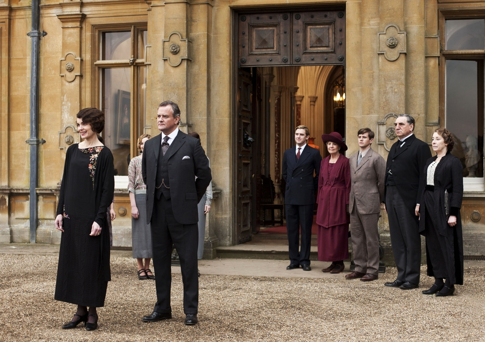 This undated publicity photo provided by PBS shows, from left, Elizabeth McGovern as Lady Grantham, Hugh Bonneville as Lord Grantham, Dan Stevens as Matthew Crawley, Penelope Wilton as Isobel Crawley, Allen Leech as Tom Branson, Jim Carter as Mr. Carson, and Phyllis Logan as Mrs. Hughes, from the TV series, Downton Abbey. Focus Features said Friday, July 13, that it will this summer begin production on a Downton film that will reunite the Crawley family on the big screen. Series creator Julian Fellowes wrote the screenplay and will produce. (AP Photo/PBS, Carnival Film & Television Limited 2012 for MASTERPIECE, Nick Briggs)