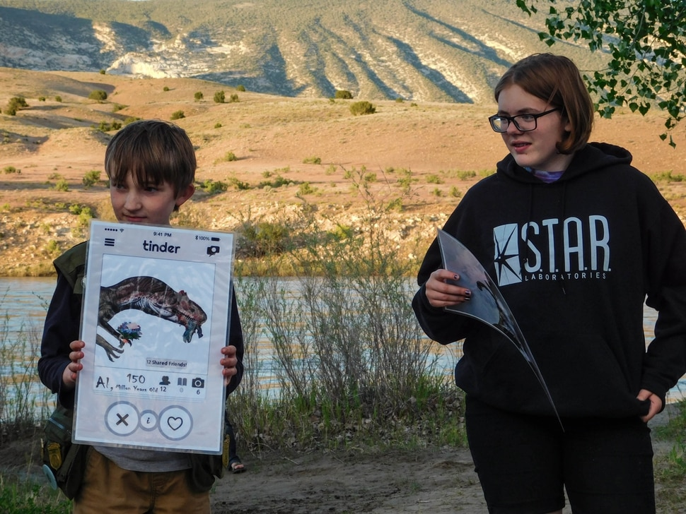 Erin Alberty | The Salt Lake Tribune Jack OÕKeefe, 9, hoists the Tinder profile of an Allosaurus during a Òdating gameÓ at a May 27, 2017, campground program. Rangers were teaching kids about dinosaur mating behaviors at Dinosaur National Monument.