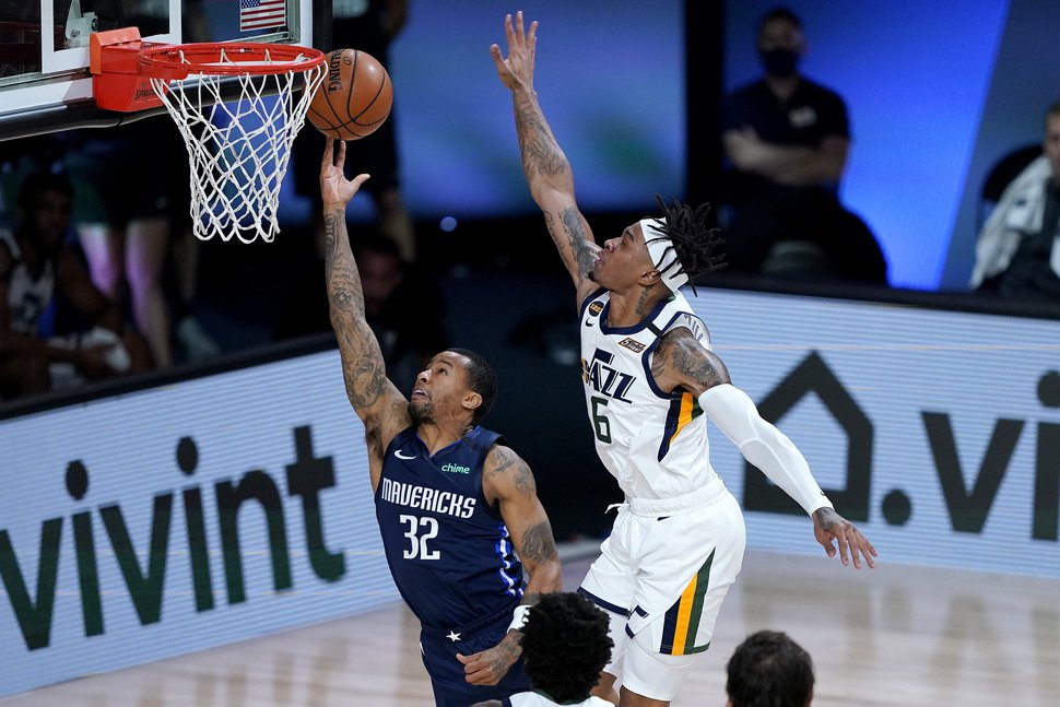 Dallas Mavericks Trey Burke (32) shoots under Utah Jazz's Rayjon Tucker (6) during the second half of an NBA basketball game Monday, Aug. 10, 2020, in Lake Buena Vista, Fla. (AP Photo/Ashley Landis, Pool)