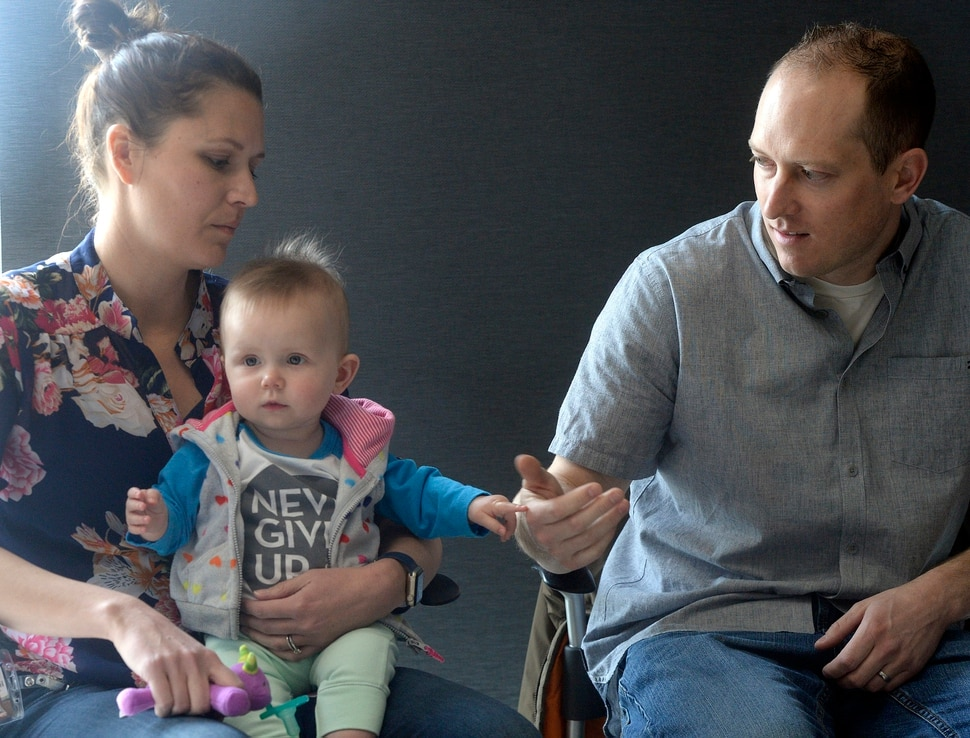 Al Hartmann | The Salt Lake Tribune Janell and Elliot Lewis play with their baby Evie at a press conference at the Utah Public Health Laboratory Wednesday Jan. 31. Evie was was tested for spinal muscular atrophy because the Lewis' first daughter Blakely died from the genetic mutation. Evie received treatment for the condition early on. The Utah Department of Health announced they're going to start testing every infant born in the state for spinal muscular atrophy. The neurodegenerative disease is the leading genetic cause of death for infants, affecting one in 11,000.