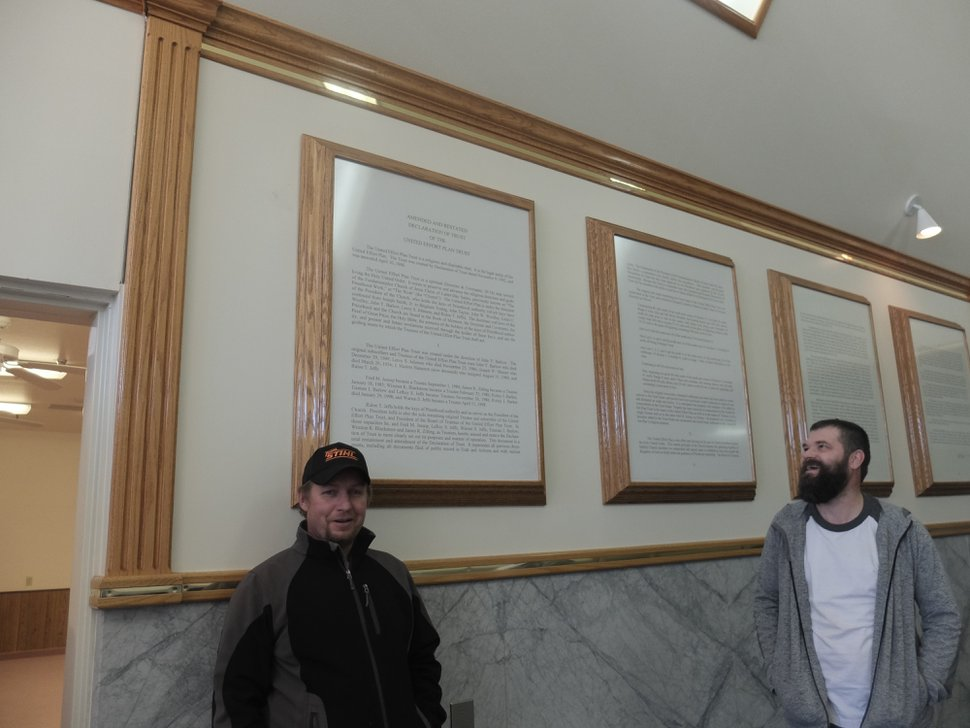 (Nate Carlisle | The Salt Lake Tribune) Simeon Holm, left, and Rulon Steed stand beneath posters describing the legal terms of the United Effort Plan hanging in the Leroy S. Johnson Meetinghouse. Holm and Steed attended a March 16, 2019, open house at what locals call