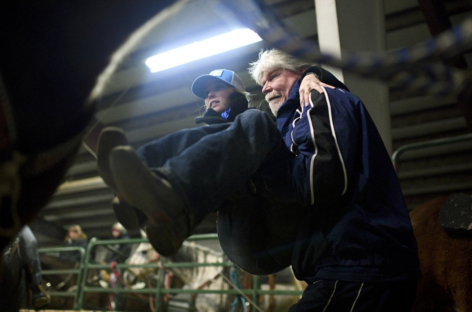 (Isaac Hale | The Daily Herald file photo) In this Jan. 7, 2017, file photo, Cory Snyder lifts his daughter Amberley up onto the saddle of her horse named Legacy, also known as French Open, before competing in the Dash for Cash barrel races at the Spanish Fork fairgrounds in Spanish Fork, Utah. Snyder has no feeling in her legs, but the barrel-racer isn't letting that slow her down. Snyder, a partially paralyzed professional barrel racer, has finished filming
