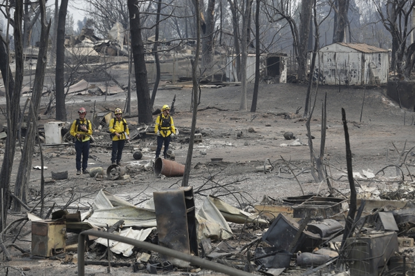 San Bernardino County Fire department firefighters assess the damage to a neighborhood in the aftermath of a wildfire, Sunday, July 29, 2018, in Keswick, Calif. (AP Photo/Marcio Jose Sanchez)