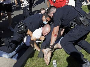 (Rick Bowmer | AP) Aaron James is arrested by Cottonwood Heights Police during a march Sunday, Aug. 2, 2020, in Cottonwood Heights, Utah. James was among eight people arrested by Cottonwood Heights Police in August. He is the father of Zane James, a 19-year-old white man who was shot and killed by a Cottonwood Heights Police officer in 2018 as he fled the scene of a robbery. Now, they are suing the city, claiming officers attacked the teen's father and brother at a peaceful protest over his death last year.