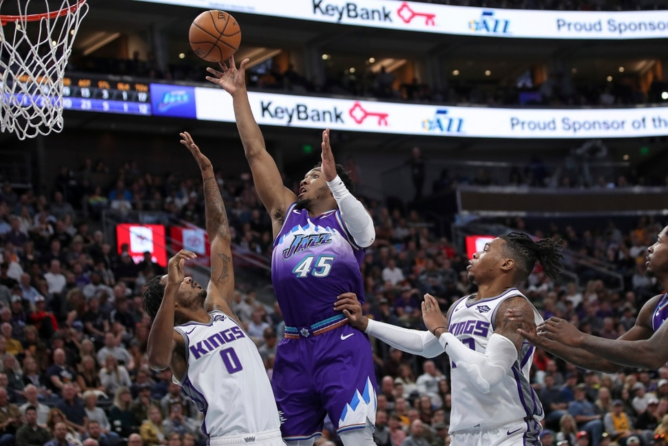 Utah Jazz guard Donovan Mitchell (45) shoots the ball between Sacramento Kings forward Trevor Ariza (0) and Sacramento Kings forward Richaun Holmes (22) during the second half of an NBA basketball game, Saturday, Oct. 26, 2019, in Salt Lake City. Utah Jazz won 113-81. (AP Photo/Chris Nicoll)