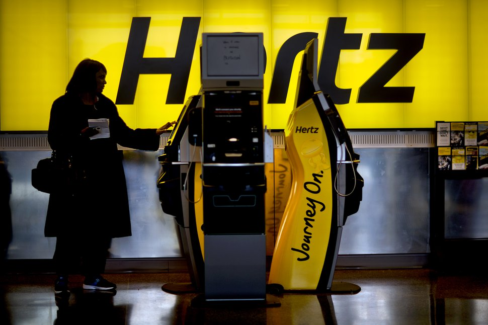 A customer checks in at a Hertz car rental counter at Hartsfield-Jackson Airport, Wednesday, Nov. 27, 2013, in Atlanta. More than 43 million people are to travel over the long holiday weekend, according to AAA. (AP Photo/David Goldman)