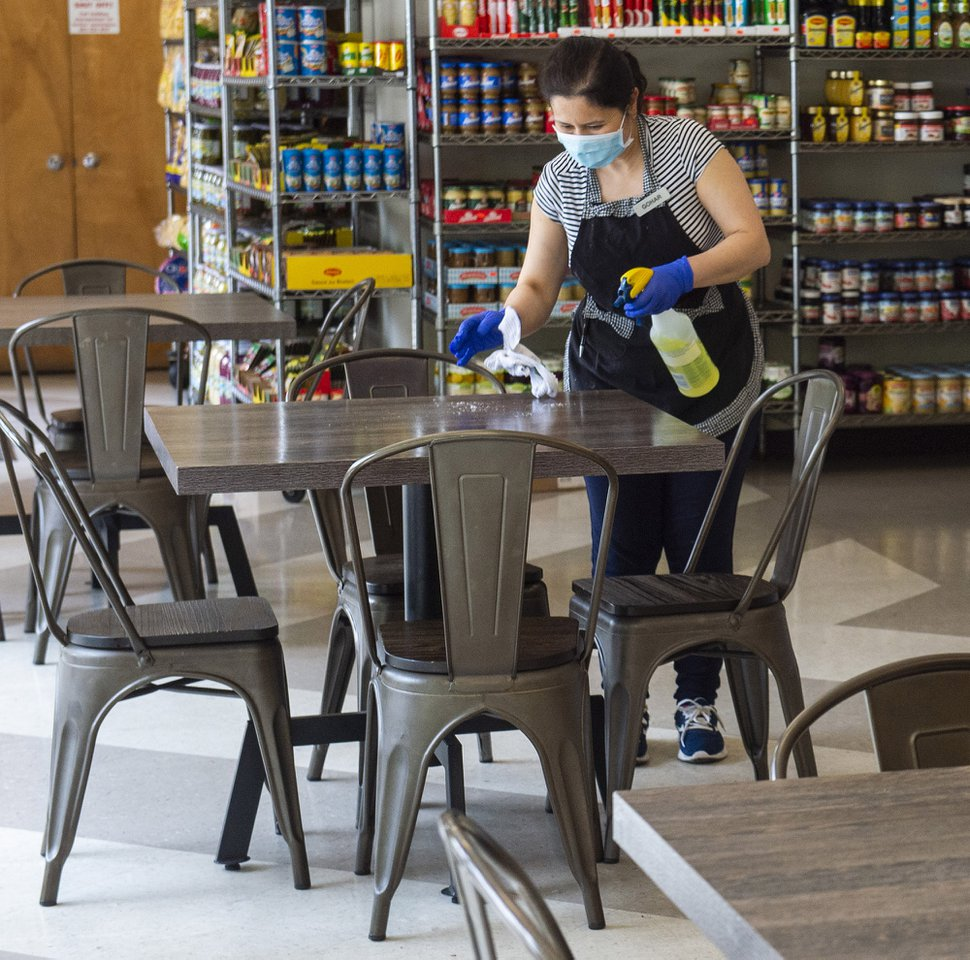 (Rick Egan | The Salt Lake Tribune) Gohar Khachajryan wipes down the tables with disinfectant between customers at Siegfried's Delicatessen, which is now open for indoor dining, Friday, May 1, 2020