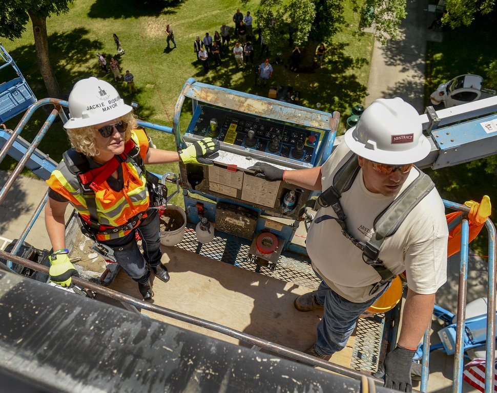 (Leah Hogsten | The Salt Lake Tribune) Mayor Jackie Biskupski (l-r) and master stone mason Jeff Eakle maneuver a lift into place to set the final capstone — carved in Eakle's likeness — in completion of the Salt Lake City and County Building rehabilitation project, Wednesday, June 13, 2018. The two-year rehabilitation restored the building's stone facade, repaired windows, and performed a seismic upgrade of the historic building built in 1894.