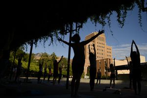 (Leah Hogsten  |  The Salt Lake Tribune) Dozens of yoga enthusiasts filled the Ogden Amphitheater on Thursday, July 25, 2019 during the annual free yoga class sponsored by the Front Yoga Loft and The Front Climbing Club. Nine instructors from the Front Yoga Loft led the crowd as the music of guitarist Julian Alvarez played in the background.