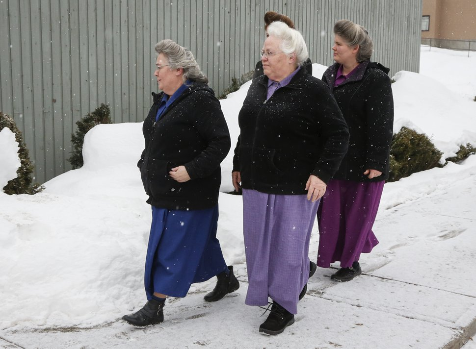 Supporters of Brandon Blackmore, Gail Blackmore and James Oler arrive at the courthouse in Cranbrook, British Columbia, Friday, Feb. 3, 2017. Two people linked to the polygamous community of Bountiful, B.C., could have foreseen that their actions would lead to a girl having sex with the church's prophet well before her 14th birthday, a B.C. Supreme Court judge said as he convicted estranged husband and wife Brandon Blackmore and Gail Blackmore Friday. He found James Oler not guilty of the same charge. (Jeff McIntosh/The Canadian Press via AP)