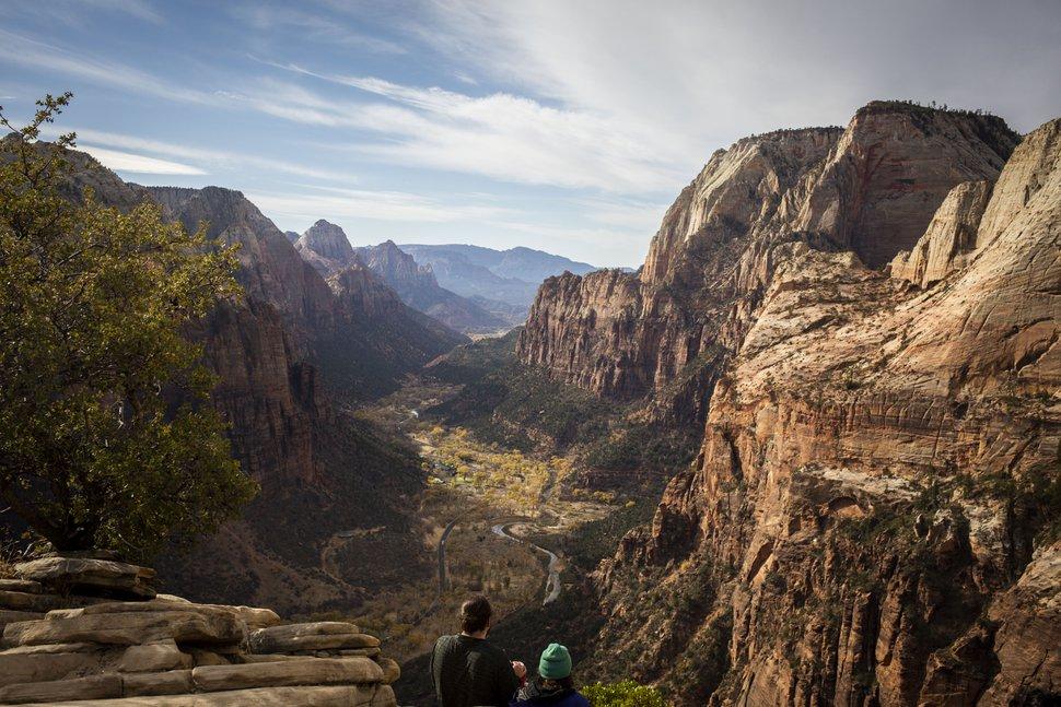 (Nikki Boliaux | The New York Times) Para pendaki menikmati pemandangan dari puncak jejak Angels Landing di Taman Nasional Zion di Utah, di mana jumlah pengunjung melonjak, 23 November 2020. Pendaki dan pendaki pemula berbondong-bondong ke alam bebas selama pandemi, tetapi beberapa tidak siap menghadapi bahaya di jalan setapak.