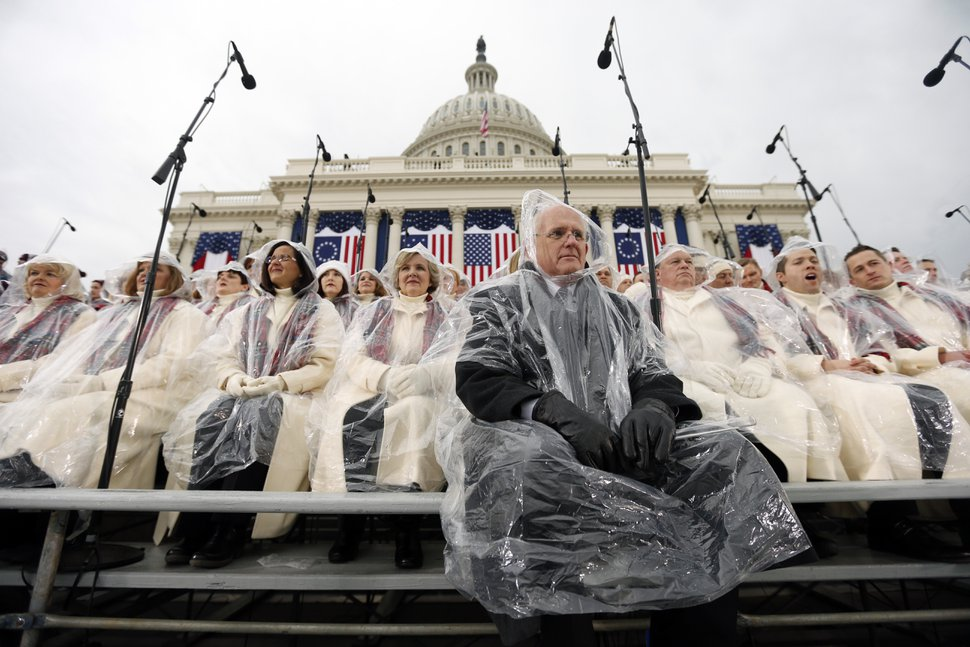 Music director Mack Wilberg, front, and members of the Mormon Tabernacle Choir sit in the rain waiting for the swearing in of Donald Trump as the 45th president of the United States to begin during the 58th Presidential Inauguration at the U.S. Capitol in Washington. Friday, Jan. 20, 2017 (AP Photo/Carolyn Kaster)