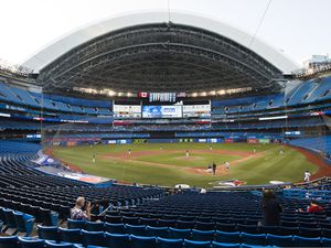 Photographers cover the game in an empty stadium during fourth-inning baseball game action in Toronto, Friday, July 17, 2020. (Nathan Denette/The Canadian Press via AP)