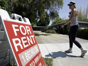 "(Paul Sakuma | AP file photo) In this July 19, 2006, file photo, a woman walks next to a ""For Rent"" sign at an apartment complex in Palo Alto, Calif. Utah has now passed a law giving renters limited protections against undisclosed rental fees."
