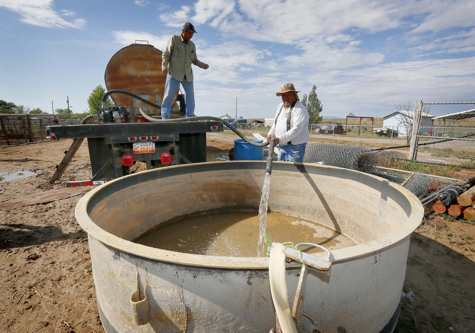 Richard Charley, right, and Melvin Jones deliver water to a ranch along the San Juan River on the Navajo Reservation, Wednesday, Aug. 12, 2015, in Shiprock, NM. Toxic wastewater from the Gold King Mine in Silverton, Colo., has contaminated the San Juan River in Northern New Mexico from the runoff of the Animas River due to an accidental breach by a mining a safety team working for the Environmental Protection Agency last week. A 100-mile-long plume has since traveled for hundreds of miles, through parts of Colorado, New Mexico and Utah on the way to Lake Powell, a key source of water for the Southwest. (AP Photo/Matt York)