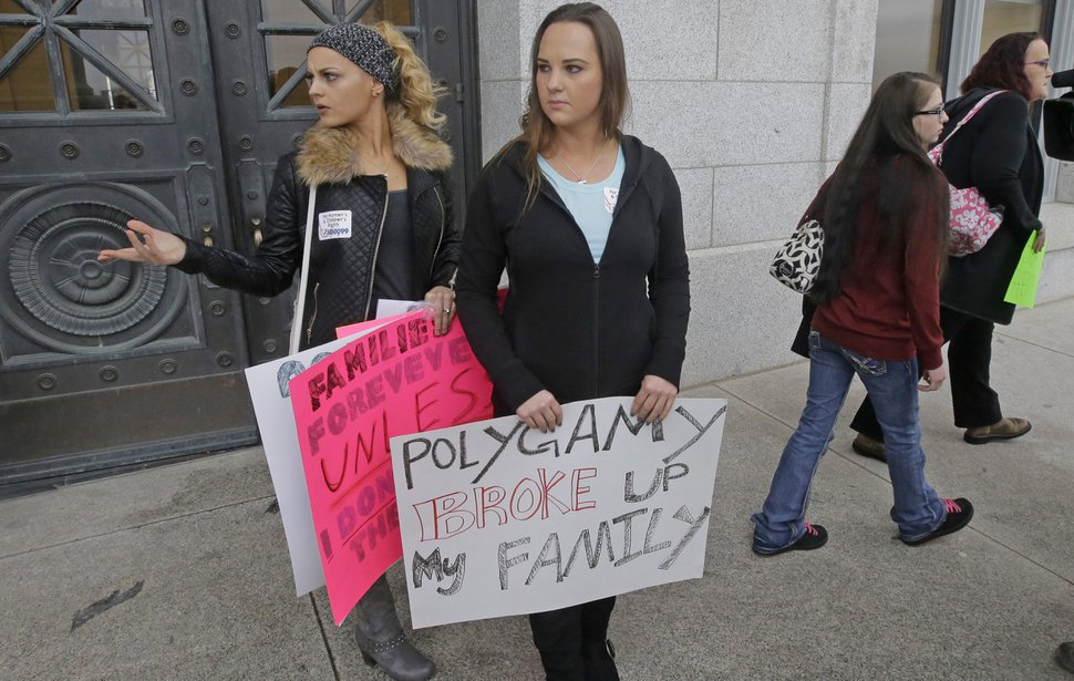 Ariel Barlow, right center, carries a sign after a news conference with former polygamists speaking in favor of Republican Rep. Mike Noel's bigamy offense amendments Friday, Feb. 10, 2017, at the Utah State Capitol in Salt Lake City. (AP Photo/Rick Bowmer)