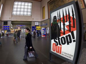 (Salvatore Di Nolfi/Keystone via AP file) A poster from the right-wing Swiss People's Party (SVP/UDC) in November 2009 depicts a woman wearing a burqa in front of a Swiss flag upon which are minarets which resemble missiles, at the central station in Geneva, Switzerland. Later in the month, a successful referendum banned the construction of new minarets in the country.