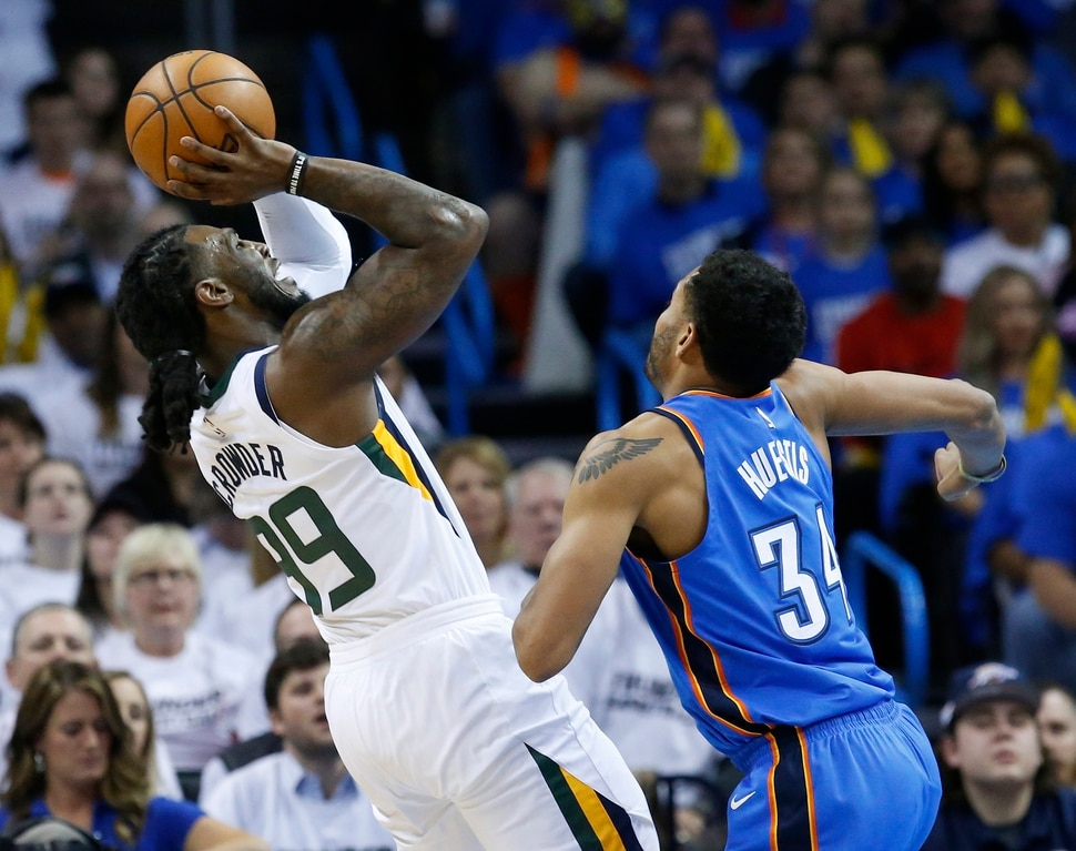 Utah Jazz forward Jae Crowder, left, shoots in front of Oklahoma City Thunder guard Josh Huestis (34) during the first half of Game 5 of an NBA basketball first-round playoff series in Oklahoma City, Wednesday, April 25, 2018. (AP Photo/Sue Ogrocki)
