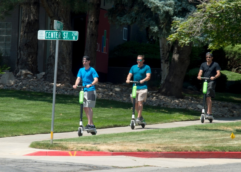 (Rick Egan | The Salt Lake Tribune) James Teague, Lee Myers, and Mike Ceja, ride Lime Scooters, in downtown Salt Lake City, Monday, July 30, 2018.