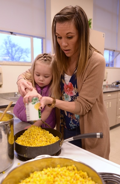 (Leah Hogsten | The Salt Lake Tribune) Granite Park Junior High assistant principal Megan Madsen empties cans of corn with her daughter Harper, 3. Sixteen members of Granite Park Junior High SchoolÕs faculty prepared and served a hot spaghetti meal to students and their families, Friday, December 22, 2017 at the school for the inaugural ÔDinner at the Park.' Roughly 90 percent of students who attend Granite Park Junior High in South Salt Lake qualify for free or reduced lunch through the federal school lunch program. Knowing the challenges faced by their students, staff members at Granite Park came up with an idea to help families through the holidays.