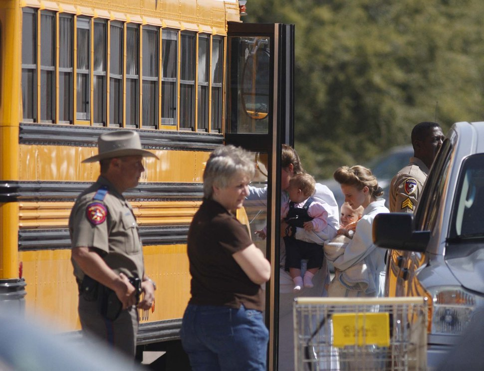 Trent Nelson | The Salt Lake Tribune FLDS women and children from the YFZ ranch are escorted by Texas Child Protective Services workers and Schleicher County Sheriff's deputies from the First Baptist Church's Fellowship Hall to buses on Sunday.
