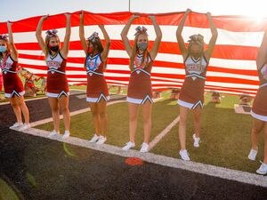 (Trent Nelson  |  The Salt Lake Tribune) Herriman cheerleaders hold a flag during the national anthem while hosting Davis High School football, in Herriman on Thursday, Aug. 13, 2020. A new study, which used COVID-19 case data from last summer from Utah and five other states, found teens and young adults have a higher chance of getting infected with the coronavirus than older adults.
