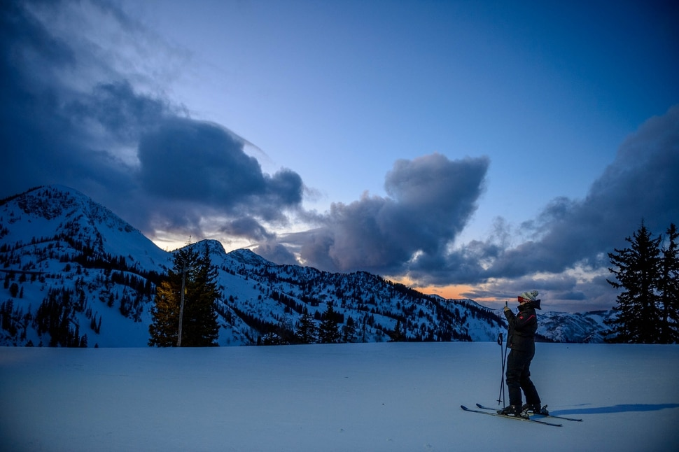 (Trent Nelson | The Salt Lake Tribune) A skier photographs the fading sunset during a night skiing session at Brighton on Monday, Feb. 24, 2020.