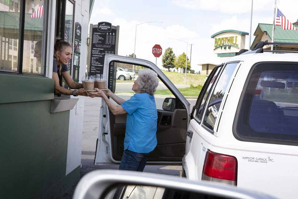 (Janie Osborne | The New York Times) A customer picks up an order of coffee at Montana Mudd in Billings, Mont., May 26, 2020. Montana Mudd's employees' head count and hours have stayed fairly constant, according to the owner, Tanya Weinreis, and she expects to have her loan through the federal government's Paycheck Protection Program fully forgiven and even hired several new workers in May and is cautiously optimistic heading into the summer.