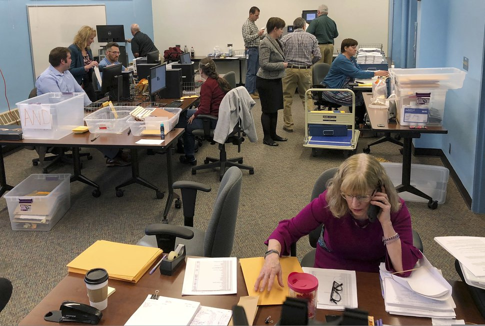 Maine election officials, including Democratic Deputy Secretary of State Julie Flynn, right, began counting ballots on Friday, Nov. 9, 2018, in Augusta for the Second Congressional District's House election. The election is the first congressional race in American history to be decided by the ranked-choice voting method that allows second choices. (AP Photo/Marina Villeneuve)