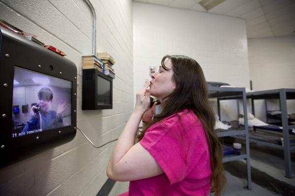 Inmate Krystle Sweat blows a kiss to her son Robby, 10, during a video conference as he visits her at the Campbell County Jail in Jacksboro, Tenn., Wednesday, March 28, 2018. There are no face-to-face visits other than exceptional circumstances. Robby hasn't hugged or even touched his mother since Christmas Day 2015, just before Sweat wound up back behind bars. He says that on the day she's released, he wants to show her how he can ride no-hands on his bike. Sweat laughs but knows their reunion must wait. (AP Photo/David Goldman)