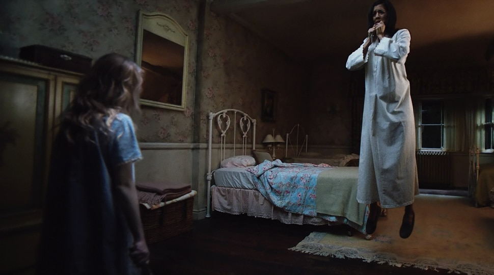 ( ! Warner Bros. Pictures) A possessed Janice (Talitha Bateman, left) suspends Sister Charlotte (Stephanie Sigman) in midair in