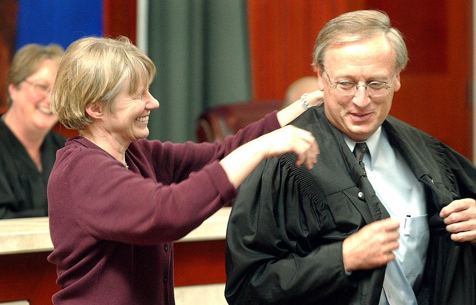 With Chief Justice Christine M. Durham looking on, Dr. Kristina Hindert puts the judicial robes on her husband Ronald E. Nehring after he took the oath of office to become Utah's newest Supreme Court Justice. photo: fraughton 6/4/03