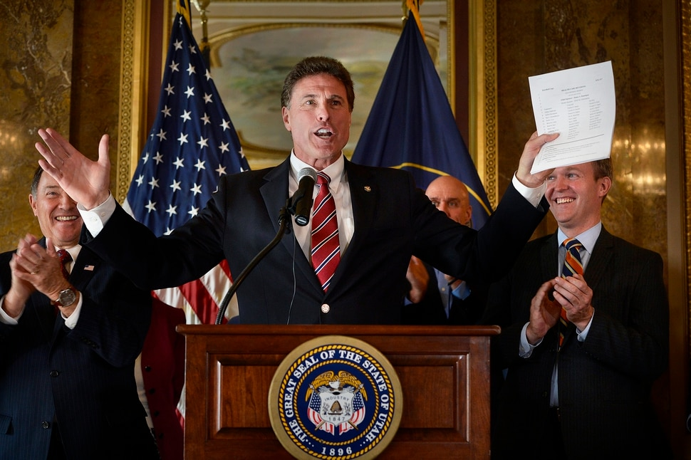 (Scott Sommerdorf | The Salt Lake Tribune) Representative Jim Dunnigan, R-Taylorsville, lets loose with an exuberant bit of celebration from the podium as he discusses his long efforts to get this Medicaid expansion done in Utah. Utah Governor Gary Herbert reacts at left, along with Salt Lake County Mayor Ben McAdams at right, Wednesday, November 1, 2017.
