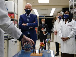 Dr. Barney Graham, left, speaks as President Joe Biden listens during a visit to the Viral Pathogenesis Laboratory at the National Institutes of Health (NIH), Thursday, Feb. 11, 2021, in Bethesda, Md. Kizzmekia Corbett, an immunologist with the Vaccine Research Center at the NIH, right, and NIH Director, second from right, listen. (AP Photo/Evan Vucci)