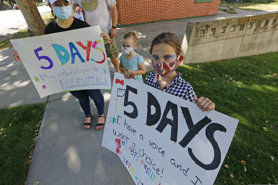 (Rick Bowmer | AP file photo) Brooke Anderson and her daughters Presley, 5, and Emma, 7, join other parents protesting the Davis School District's hybrid school reopening plan outside the Davis School District office prior to a school board meeting Thursday, Aug. 6, 2020, in Farmington, Utah. The parents would prefer their children to attend school five days a week.