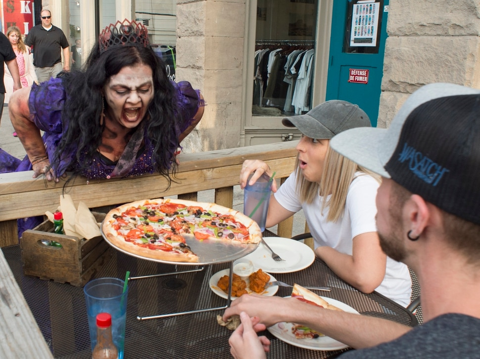 (Rick Egan | The Salt Lake Tribune) Marlana Mompus Bryan scares a couple dining on 200 South, during the 11th annual Zombie Walk, Sunday, Aug. 26, 2018.
