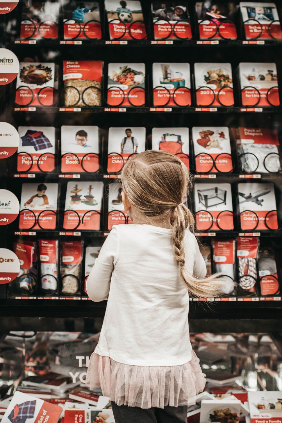 (Photo courtesy of The Church of Jesus Christ of Latter-day Saints) A girl looks at the many options available for purchase in a Giving Machine in Gilbert, Ariz. Gilbert is one of 10 locations this year where donations can be made during the Christmas season.