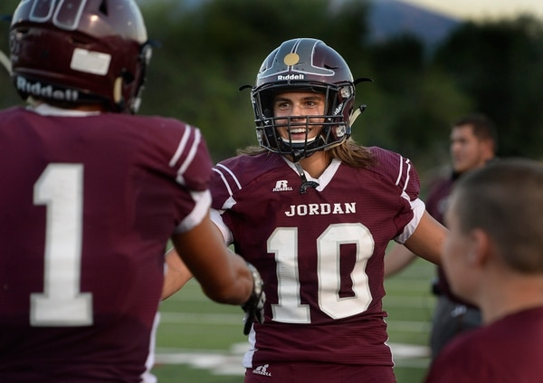 Scott Sommerdorf | The Salt Lake Tribune Jordan QB Crew Wakley smiles as he congratulates Isaiah Jackson for a TD catch to give Jordan their 3rd TD, and a 21-0 lead over Desert Hills at the half, Friday, August 19, 2016.